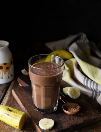Chocolate banana smoothie with sliced banana and milk