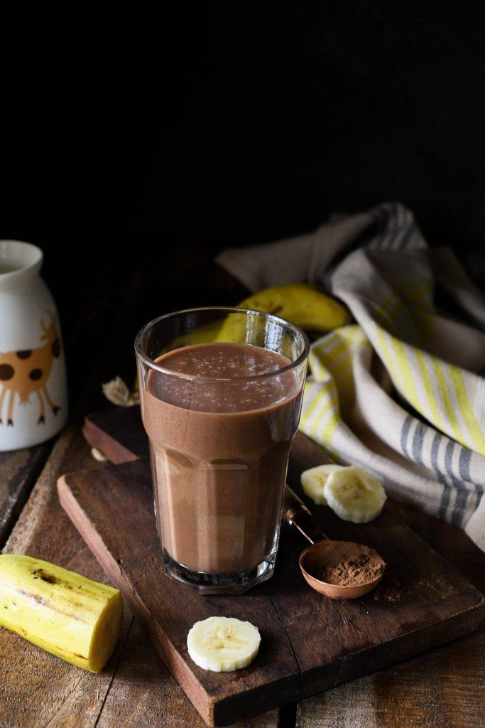 Chocolate banana smoothie with sliced banana, cocoa powder and milk