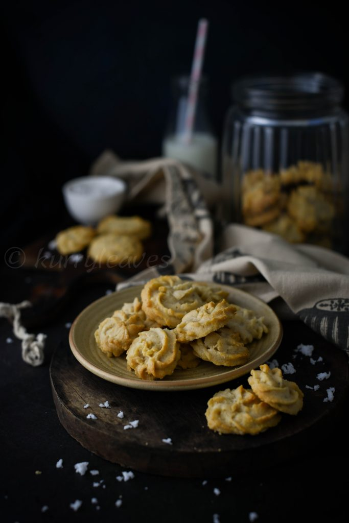 eggless wheat cookies on a platter with milk and cookie jar